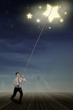 Businessman pulling stars Royalty Free Stock Photography