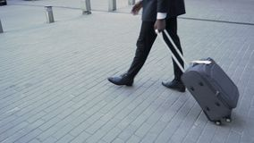 Businessman pulling suitcase at airport, business trip, first class travelling