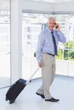 Businessman pulling suitcase and talking on phone smiling at cam Royalty Free Stock Photo