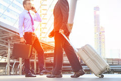Businessman pulling suitcase walking in modern city Royalty Free Stock Images