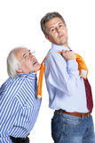Businessman pulling a tie to older man Royalty Free Stock Photo