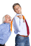 Businessman pulling a tie to older man Royalty Free Stock Image
