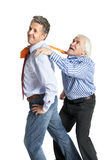 Businessman pulling a tie to older man Stock Photography