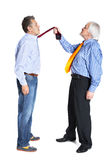 Businessman pulling a tie to younger man Stock Images