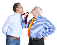 Businessman pulling a tie to younger man Stock Photo