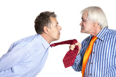 Businessman pulling a tie to younger man Royalty Free Stock Image