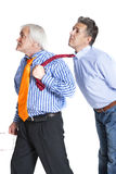 Businessman pulling a tie to younger man Stock Photos