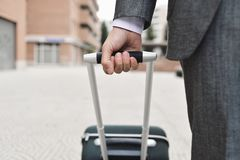 Businessman pulling a trolley case. Closeup of a young caucasian businessman in an elegant gray suit pulling a trolley by its handle on the street Stock Photos