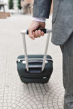 Businessman pulling a trolley case. Closeup of a young caucasian businessman in an elegant gray suit pulling a trolley by its handle on the street Stock Photo