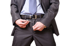 Businessman pulling a usb cable off his pants. Stock Photo