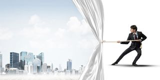Young man opening white curtain and presenting modern city landscape Royalty Free Stock Photos