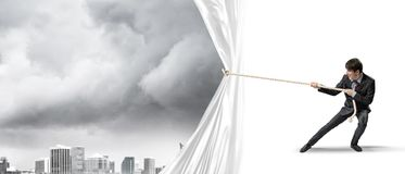 Young man opening white curtain and presenting modern city landscape Royalty Free Stock Images