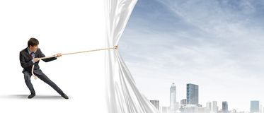 Young man opening white curtain and presenting modern city landscape Stock Photo