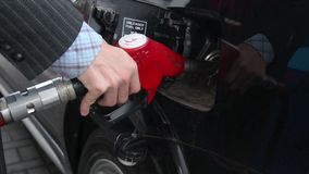 Businessman pulls out gasoline pistol fueling car petrol station. Stock footage stock footage