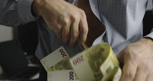 Businessman pulls out of the shirt a lot of money. Denominations: two hundred euros, one hundred euros, fifty euros, one hundred dollars stock footage