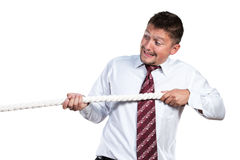 Businessman pulls on a rope. A man in a white shirt and tie himself emotionally drawn to a rope isolated on white background Stock Photography