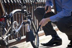 A businessman pumping up the tires on his bicycle Stock Photography
