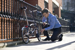 A businessman pumping up the tires on his bicycle Royalty Free Stock Photo