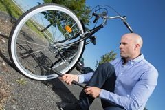 Businessman pumping up tires on bicycle. A businessman pumping up the tires on his bicycle stock images