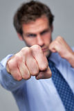 Businessman punching towards camera Stock Images