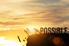 Businessman push impossible wording to possible wording on top of mountain with sunlight. Positive mindset concept