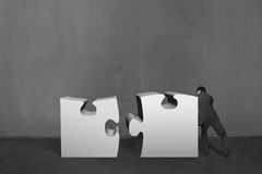 Businessman push two heavy puzzles together in concrete wall bac. Kground Stock Photo
