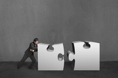 Businessman push two heavy puzzles together in concrete wall bac. Kground Stock Images