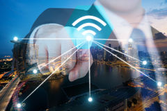 Businessman push wifi icon on city and network connection concep Stock Image