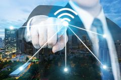 Businessman push wifi icon on city and network connection concept. Bangkok smart city and wireless communication network, abstract stock images