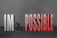 Businessman push word impossible im away, to make it possible. In concrete wall background Royalty Free Stock Image