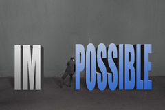 Businessman push word. Impossible possible to separate, to make it possible in concrete wall background Stock Photos