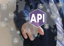 Businessman pushes a button API. Application Programming Interface on the touch screen Royalty Free Stock Photography