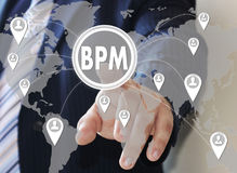 Businessman pushes a button BPM on the touch screen. With world map Royalty Free Stock Photos