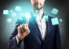 Businessman pushes on cube figure. Businessman pushes on cube figure as symbol of innovation. Over gray background stock photos