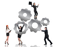 Businessman pushes gears , woman hangs on them Stock Photos