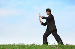 Businessman pushes standing on grass Royalty Free Stock Images