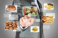 Businessman pushes touch screen button with salad on virtual interface with food. Diet concept Royalty Free Stock Photography