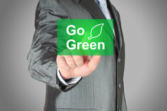 Businessman pushes touch screen go green button. Eco concept stock photo