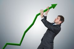 Businessman is pushing arrow in graph up. Growth and maximizing earnings concept.  Royalty Free Stock Photos