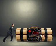 Businessman pushing big bomb with timer Stock Image