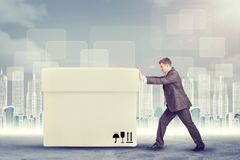 Businessman pushing big white box Royalty Free Stock Image