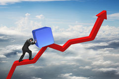 Businessman pushing blue 3D block upward on red trend line Royalty Free Stock Images