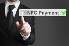 Businessman pushing button nfc payment. Businessman in black suit pushing nfc payment green checked Stock Image