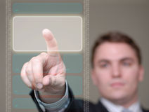 Businessman Pushing Button on Translucent Screen. Young businessman pushing a button area on a translucent, hi-tech screen. Shallow depth of field stock photos