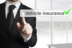Businessman pushing button vehicle insurance green check. Ed stock photo