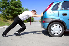 Businessman pushing a car. Man in business suit pushing a broken car or a car out of gas Stock Photo
