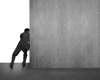 Businessman pushing concrete wall away Royalty Free Stock Images