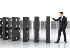 Businessman pushing dominoes Stock Photography