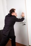 Businessman pushing the door. To prevent people entering room Stock Photos