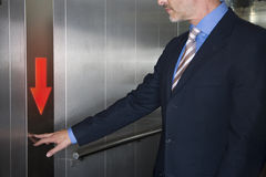 Businessman pushing down arrow on elevator Royalty Free Stock Images
